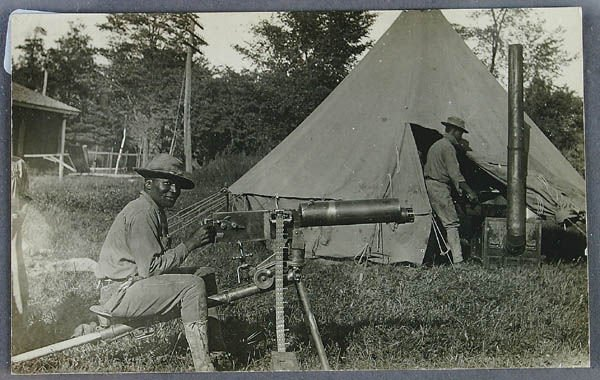 694: A BLACK REAL PHOTO POSTCARD soldier with machine