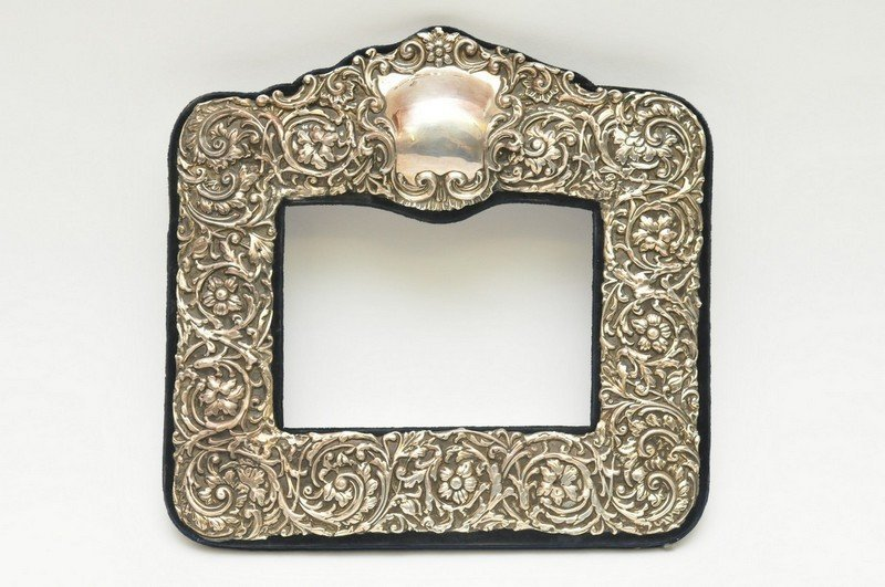 An ornate silver photo frame having raised scrolling fo