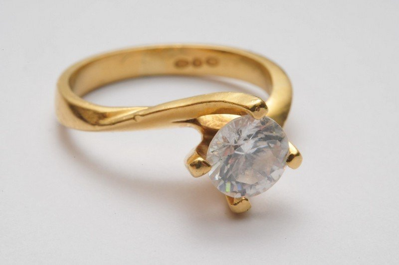 An 18ct gold crossover ring set with a single CZ solita