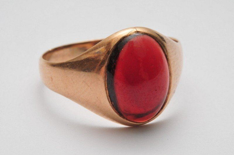 A 9ct gold ring set with a central garnet cabochon