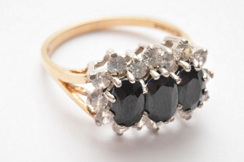 A ladies 9ct gold ring set with three sapphires and whi