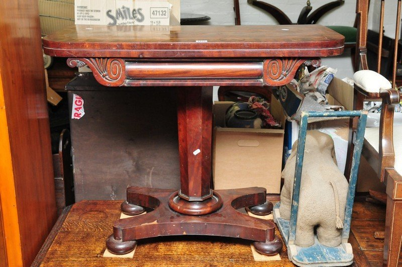 A Victorian mahogany card table supported by a tapering