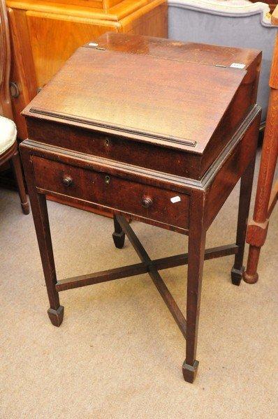 A small 19th century mahogany desk having hinged slopin