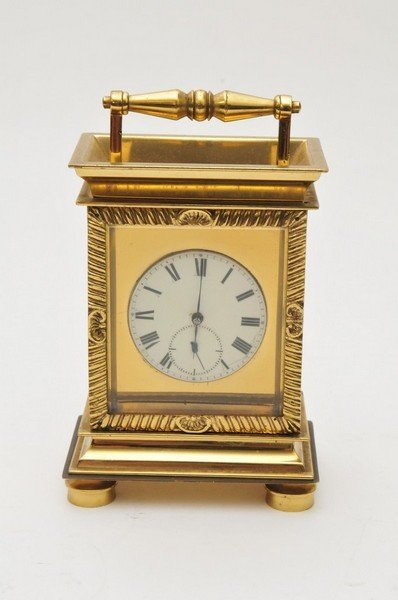 A brass carriage clock with fusee pocket watch movement