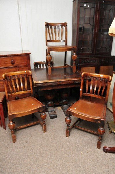 A large oak drawer leaf table with four matching chairs