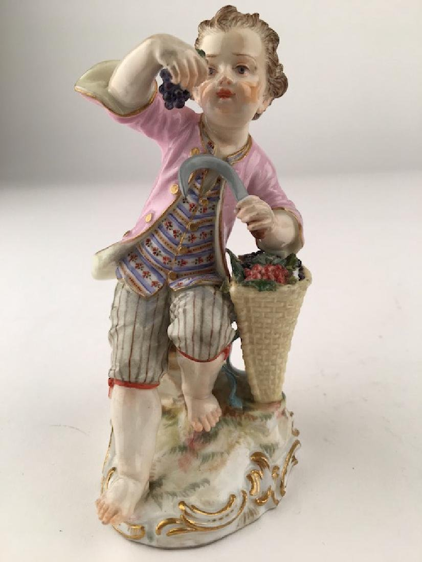 Meissen figurine of a young boy sitting on rocks with a