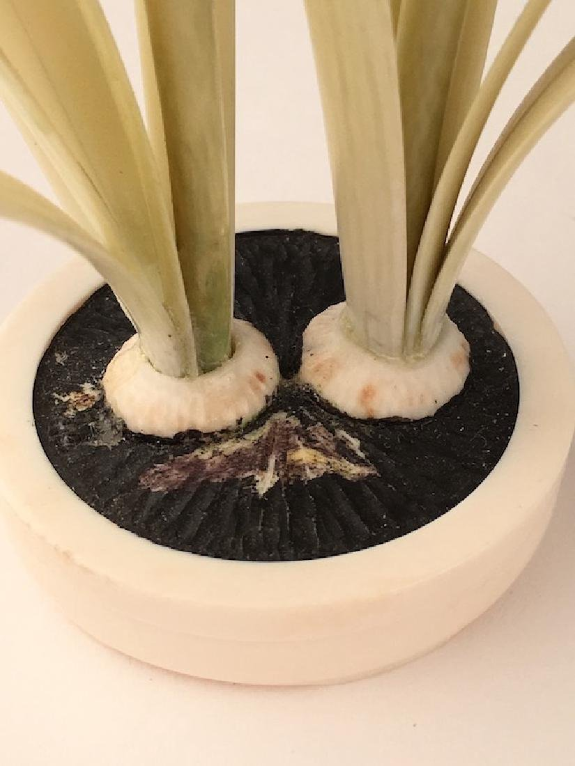 A carving of two flowering flowers in a small pot. - 3
