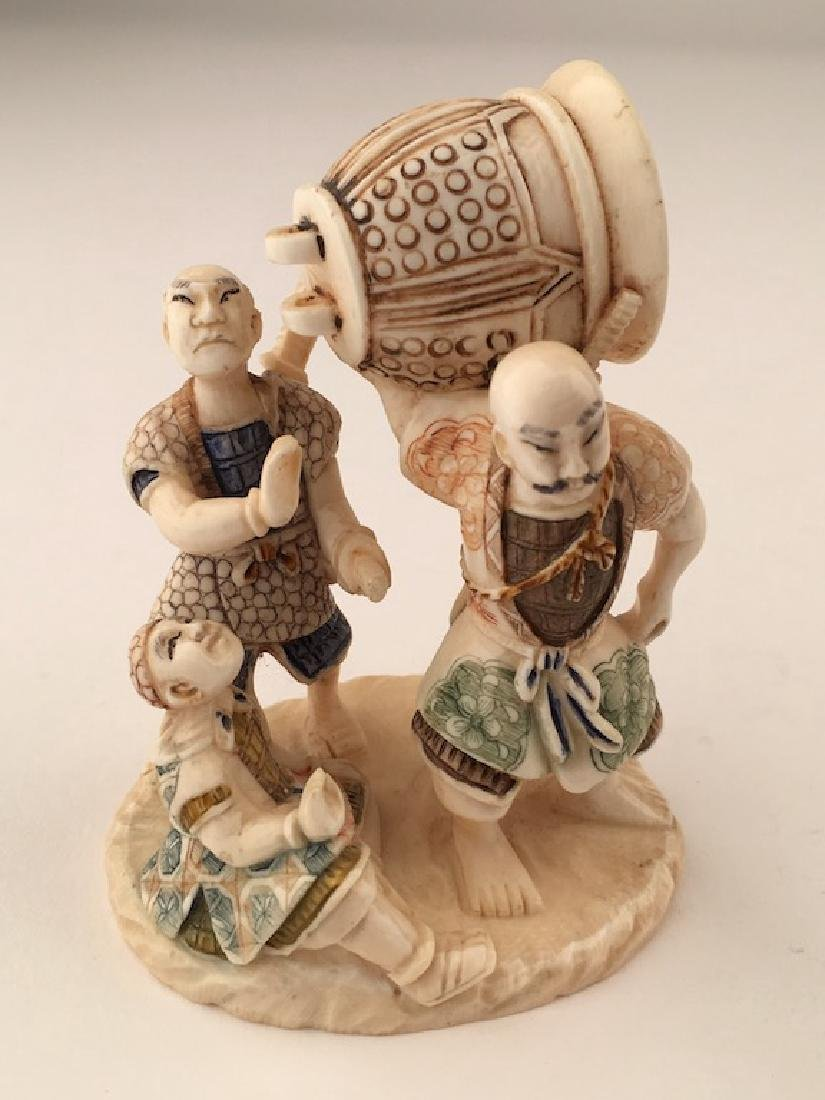 A carved figurine of three men with a large bell.