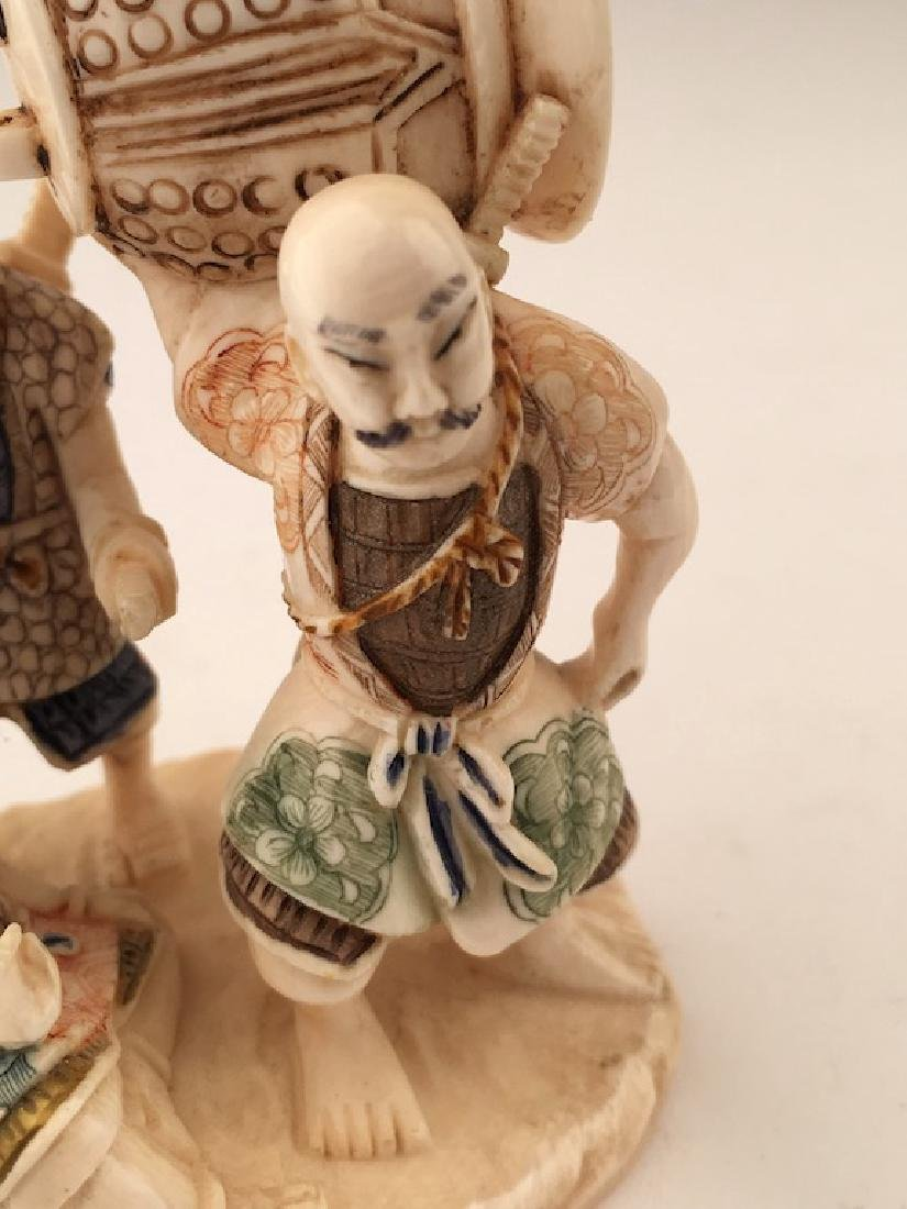 A carved figurine of three men with a large bell. - 2
