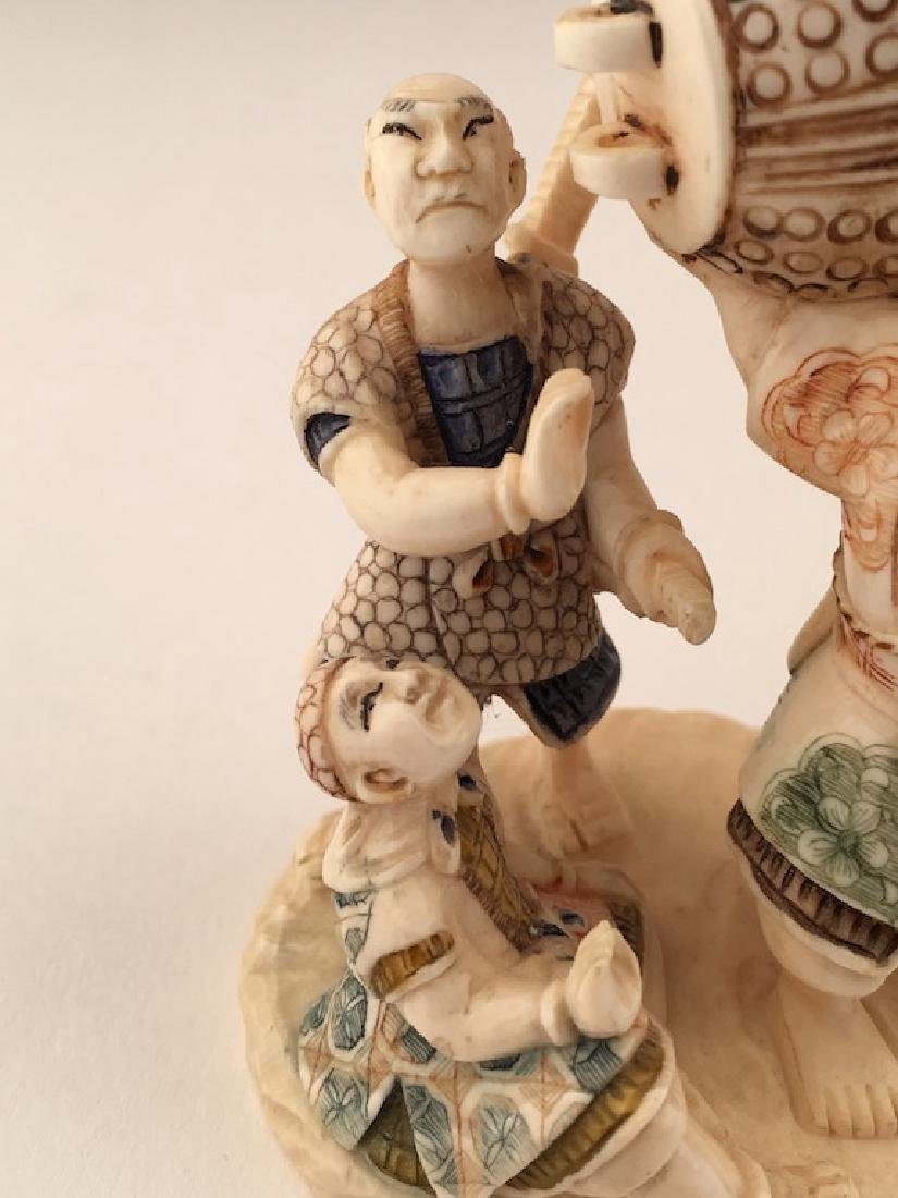 A carved figurine of three men with a large bell. - 3