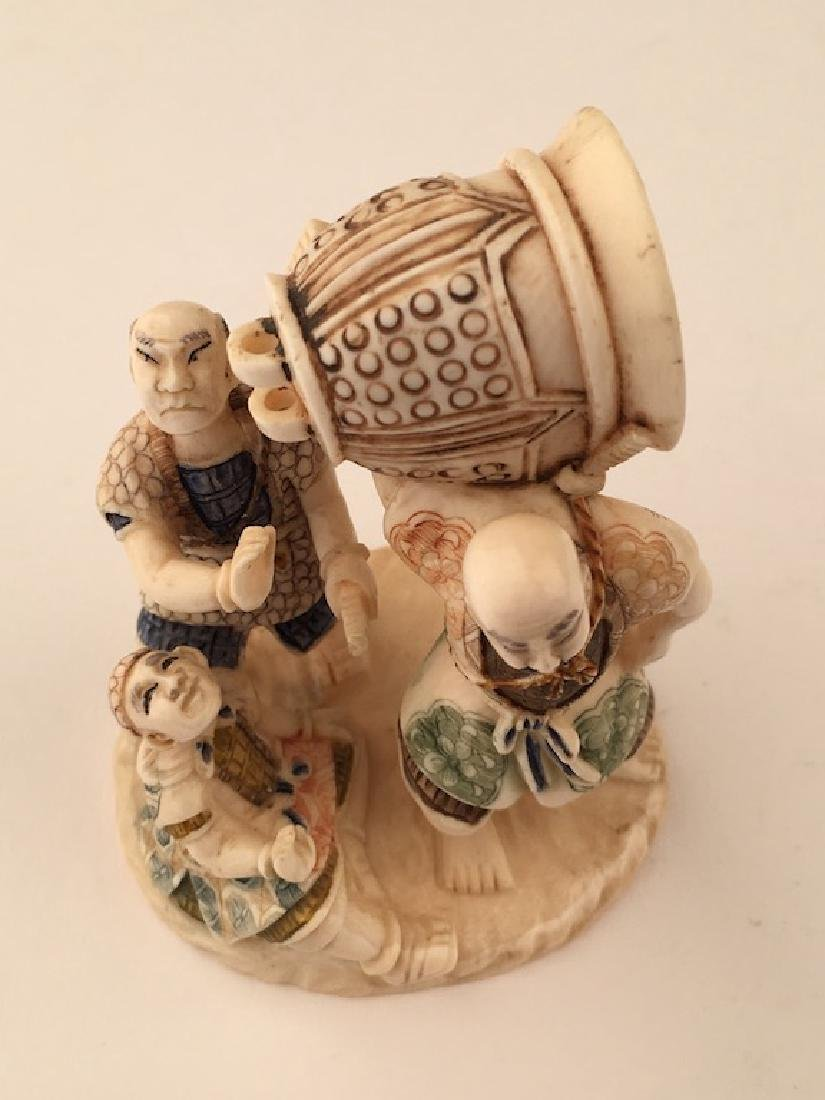 A carved figurine of three men with a large bell. - 4
