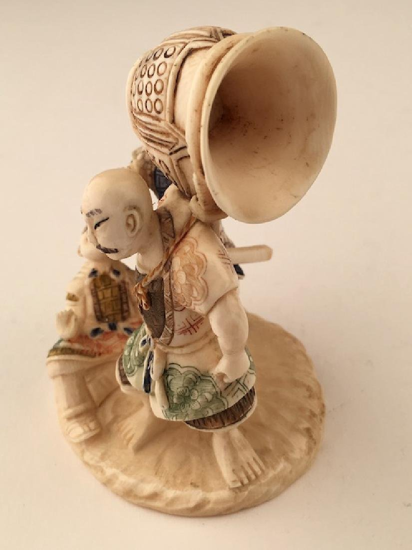 A carved figurine of three men with a large bell. - 5