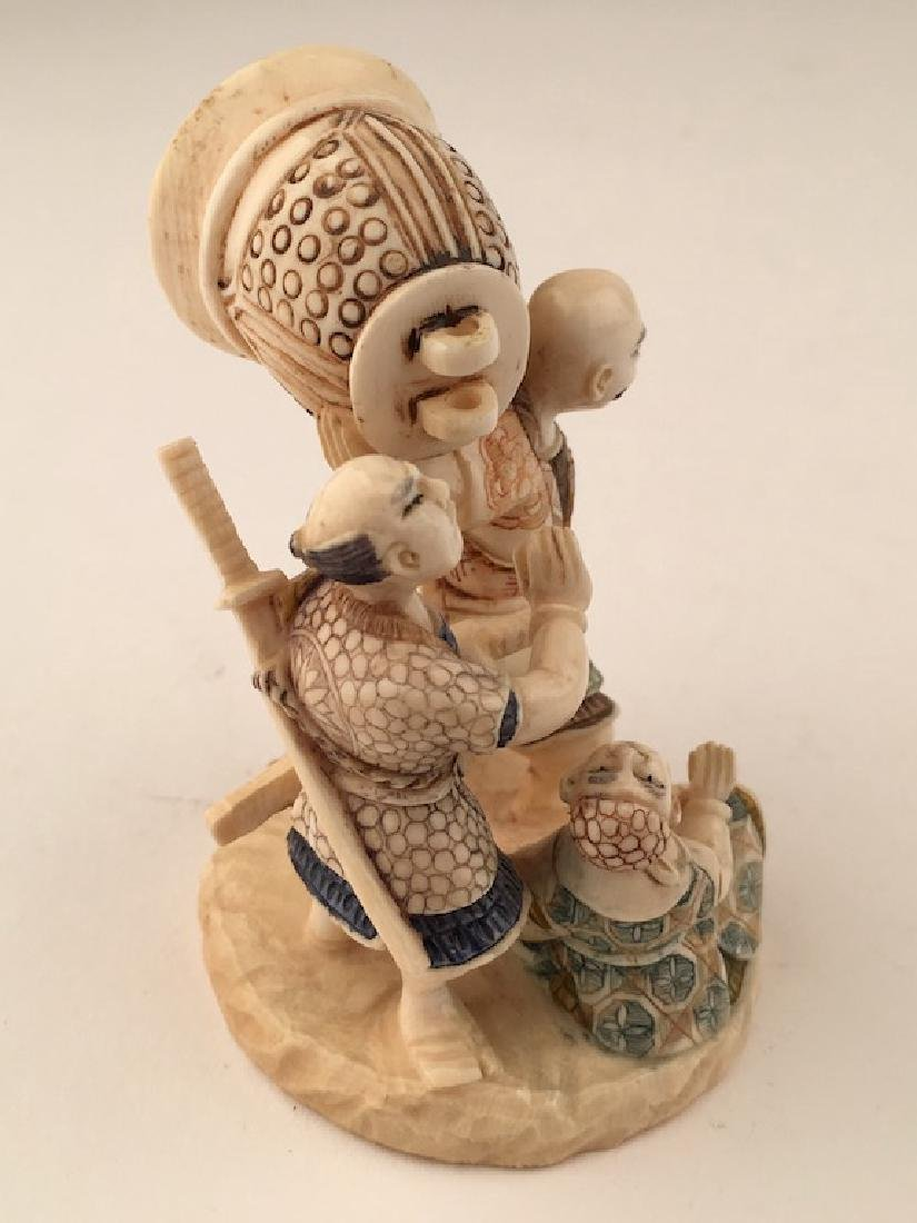 A carved figurine of three men with a large bell. - 7
