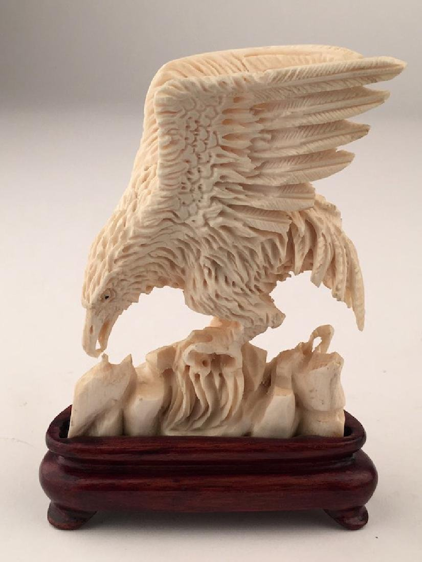 A well carved Phoenix eating while standing on rocks.