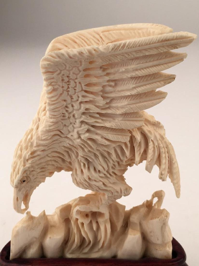 A well carved Phoenix eating while standing on rocks. - 3