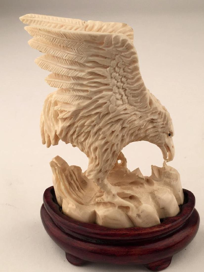 A well carved Phoenix eating while standing on rocks. - 5