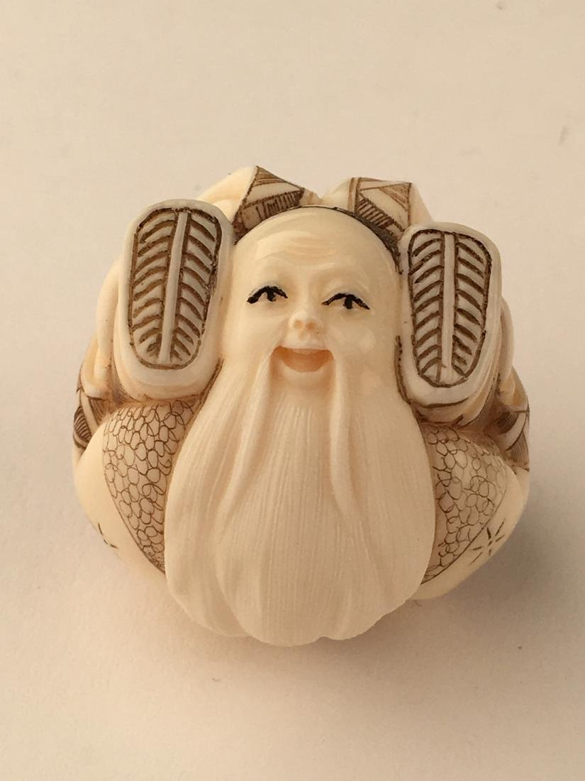 A carved netsuke figure of a man with his feet wrapped