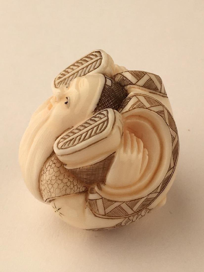 A carved netsuke figure of a man with his feet wrapped - 2