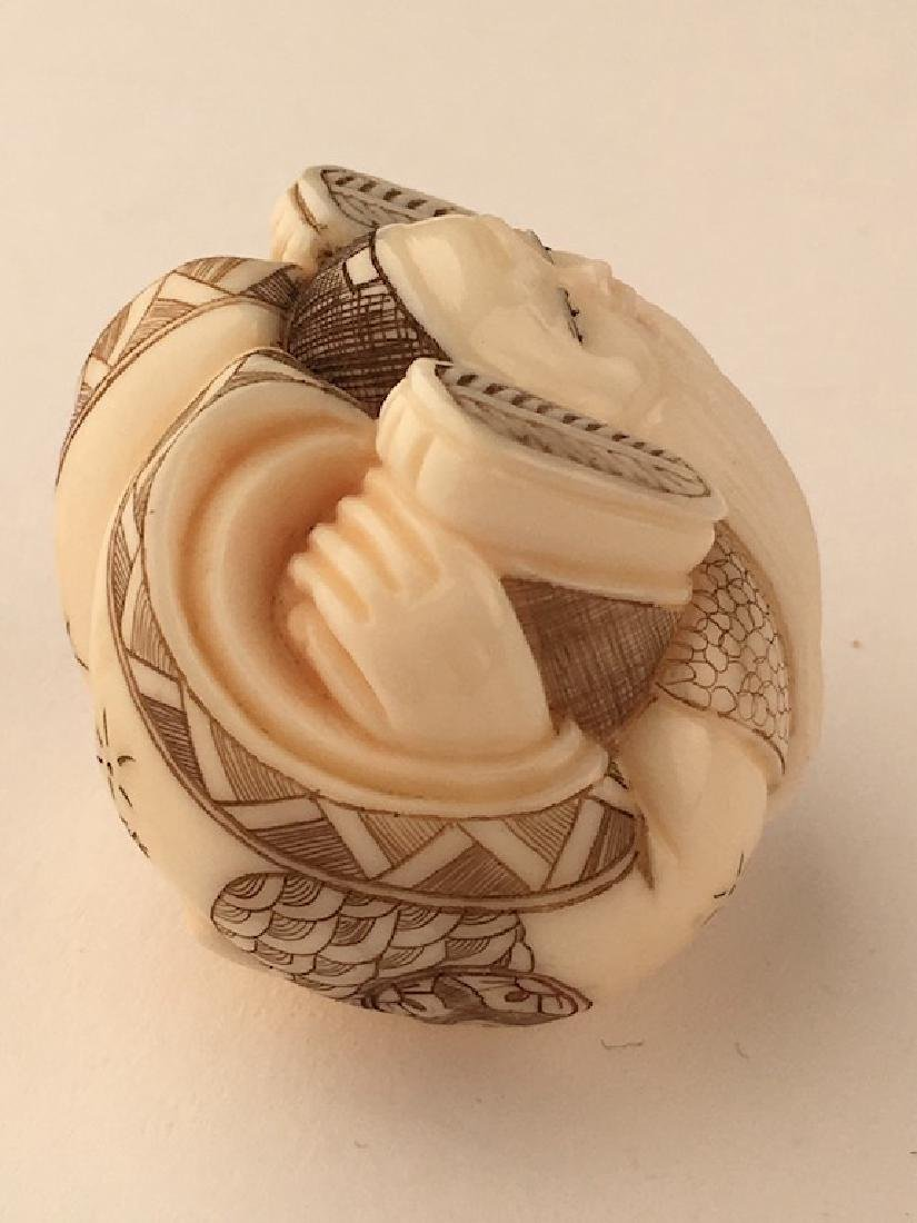 A carved netsuke figure of a man with his feet wrapped - 4