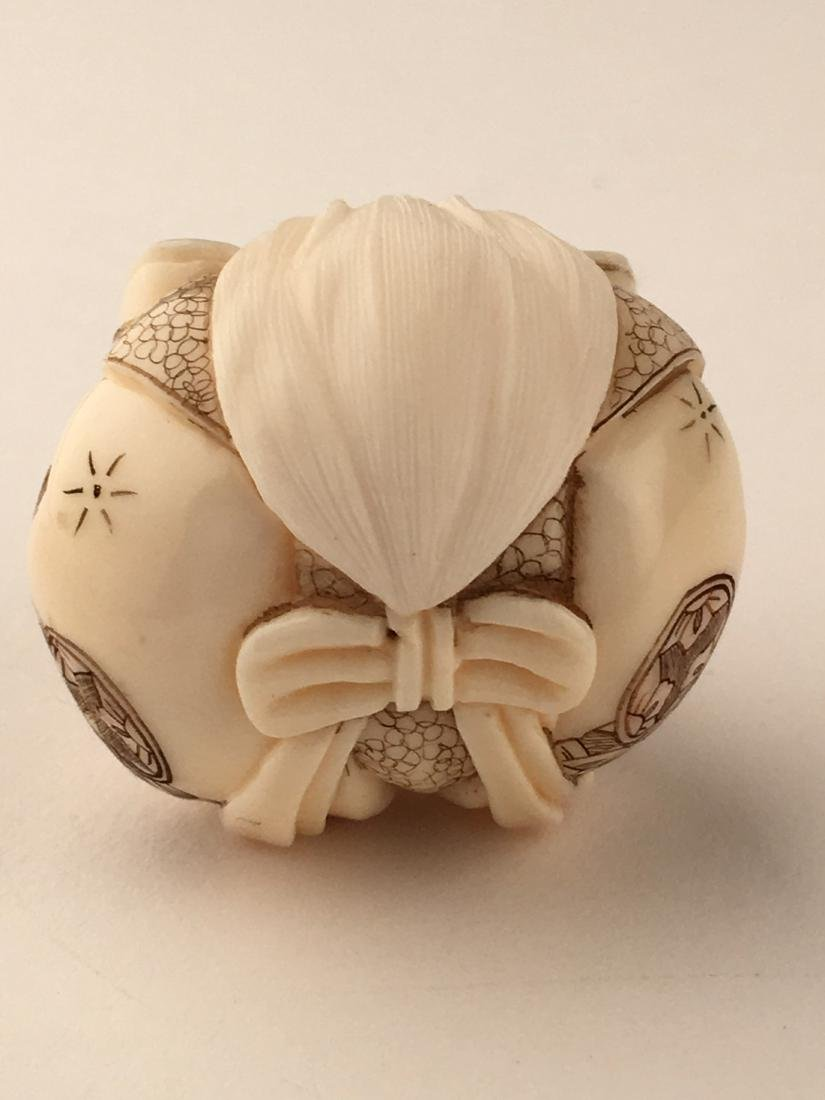 A carved netsuke figure of a man with his feet wrapped - 5