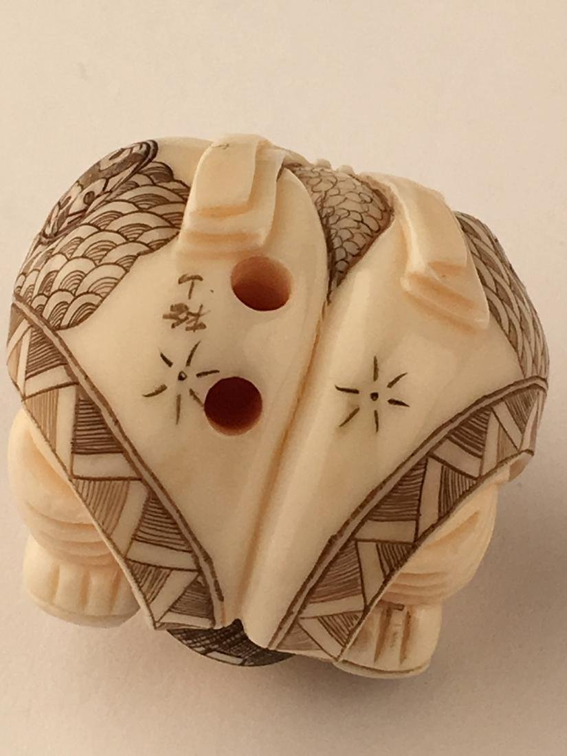 A carved netsuke figure of a man with his feet wrapped - 6