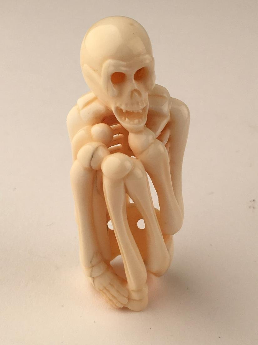 A carved netsuke figure of a skelton. Signed. Height 2m