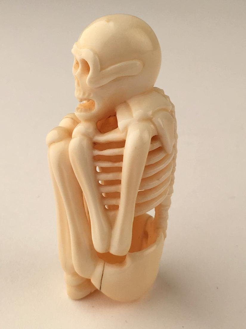 A carved netsuke figure of a skelton. Signed. Height 2m - 2