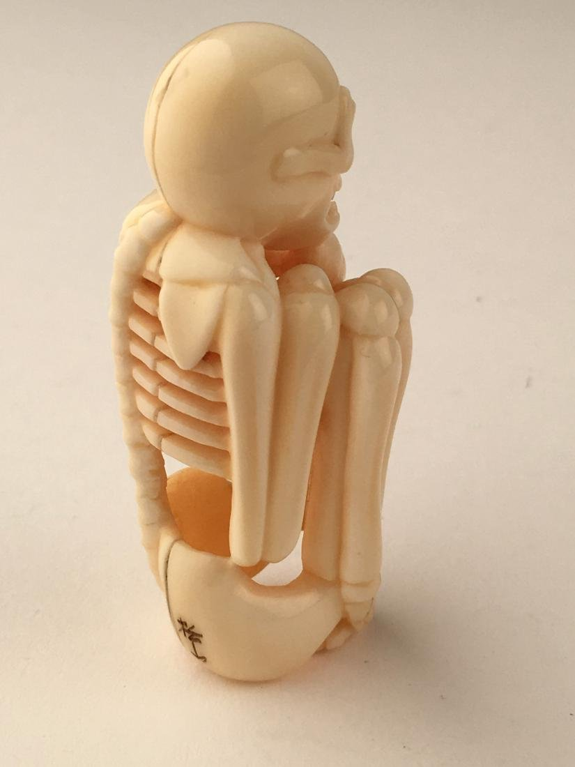 A carved netsuke figure of a skelton. Signed. Height 2m - 3