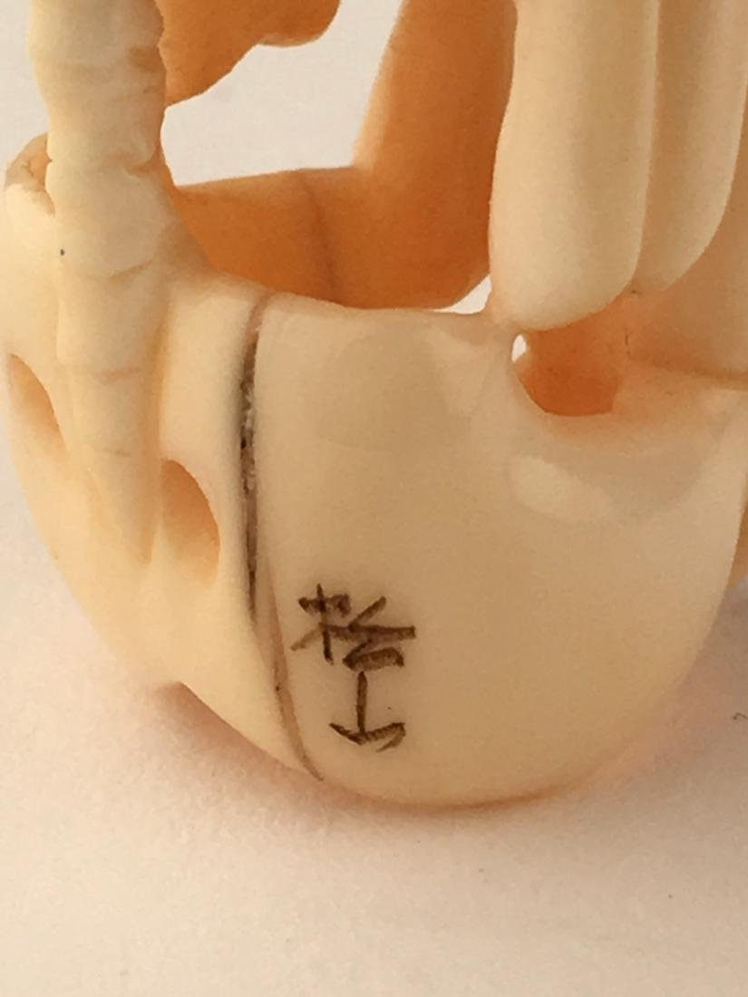 A carved netsuke figure of a skelton. Signed. Height 2m - 4