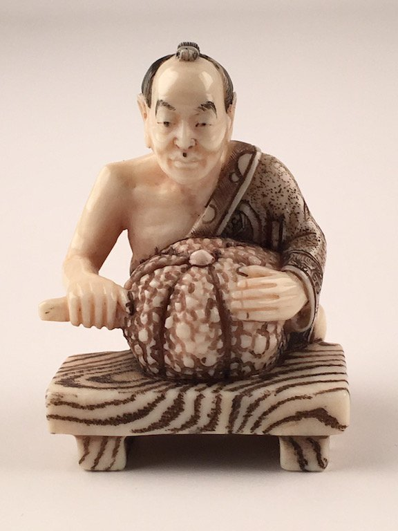 Carved netsuke figure of a man cutting a melon