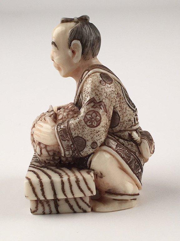 Carved netsuke figure of a man cutting a melon - 2