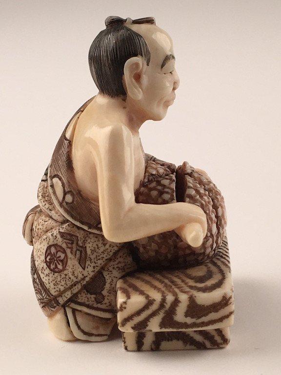Carved netsuke figure of a man cutting a melon - 4