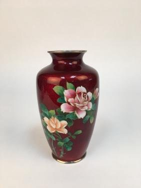 Cloisonne enameled vase with large roses on a blood red