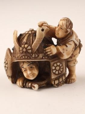 Japanese carved Netsuke of a young child hiding under a