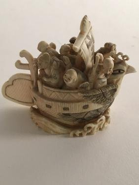 Carved figure of a boat with seven (7) people in it.