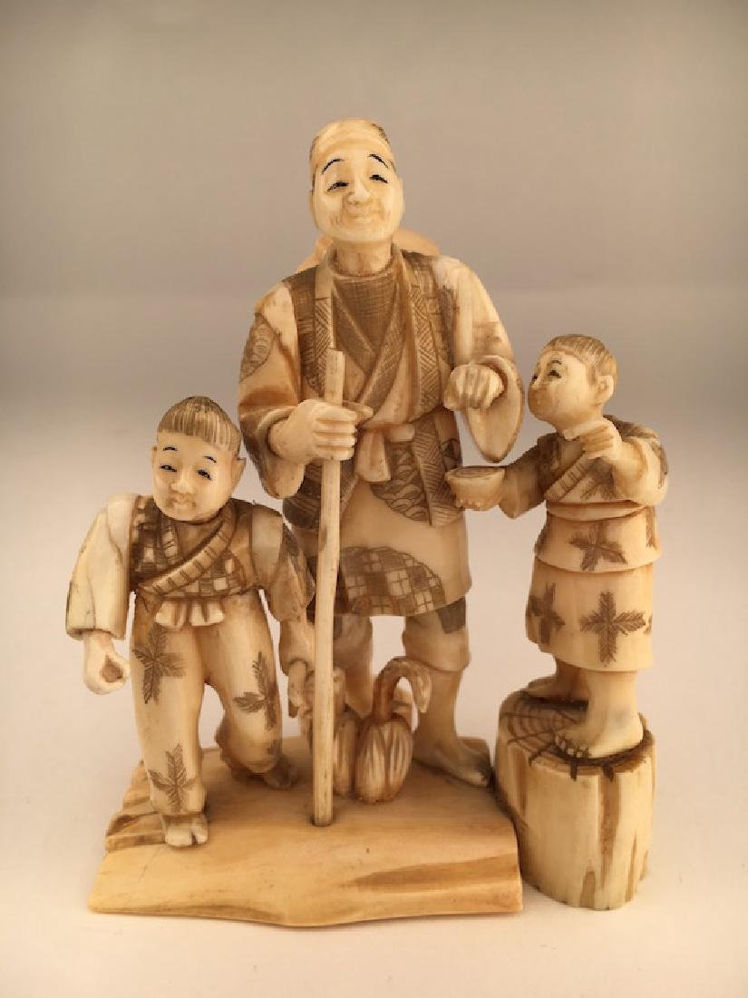 A carved figurine of a man with two young children