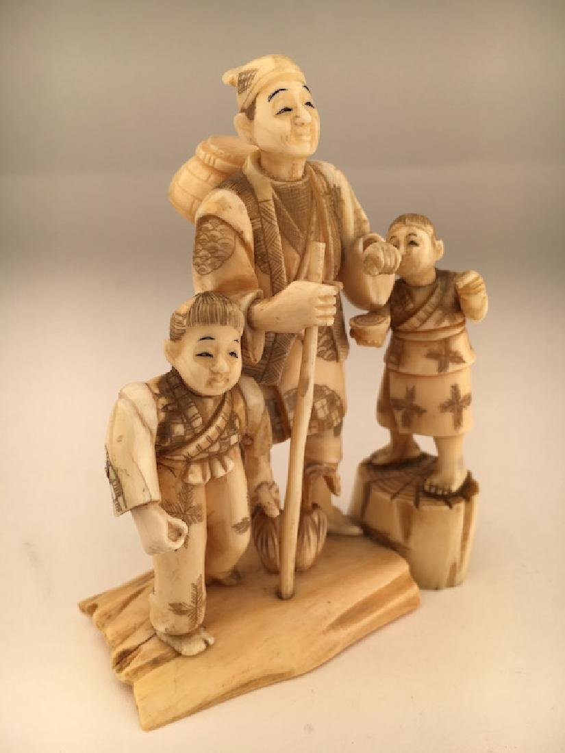 A carved figurine of a man with two young children - 3