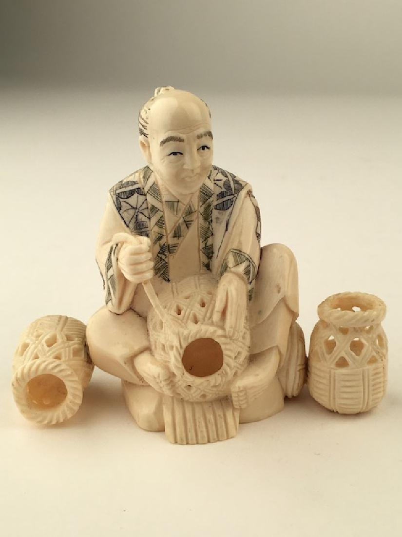 Carved Okimono figure seated and making baskets. SIgned