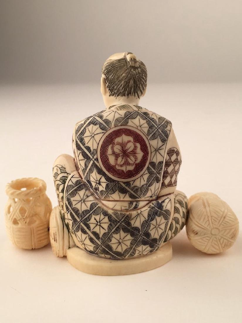 Carved Okimono figure seated and making baskets. SIgned - 5