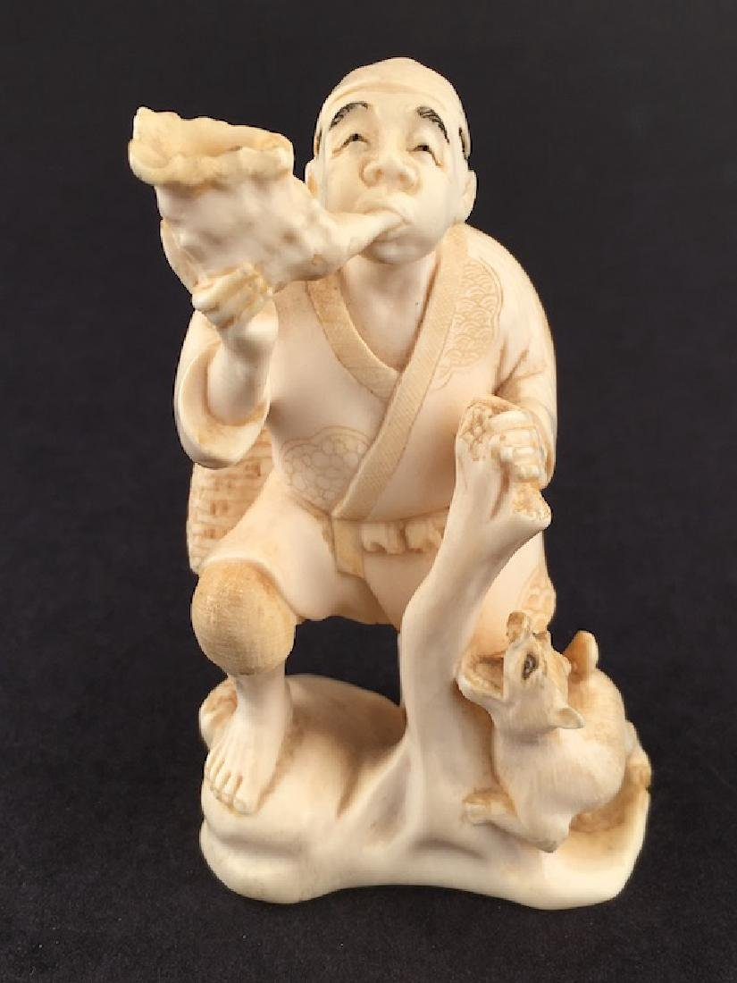 A carved man man wearing a sack and blowing into a