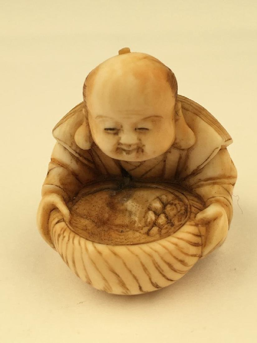 Antique carved Netsuke figure of a woman preparing food