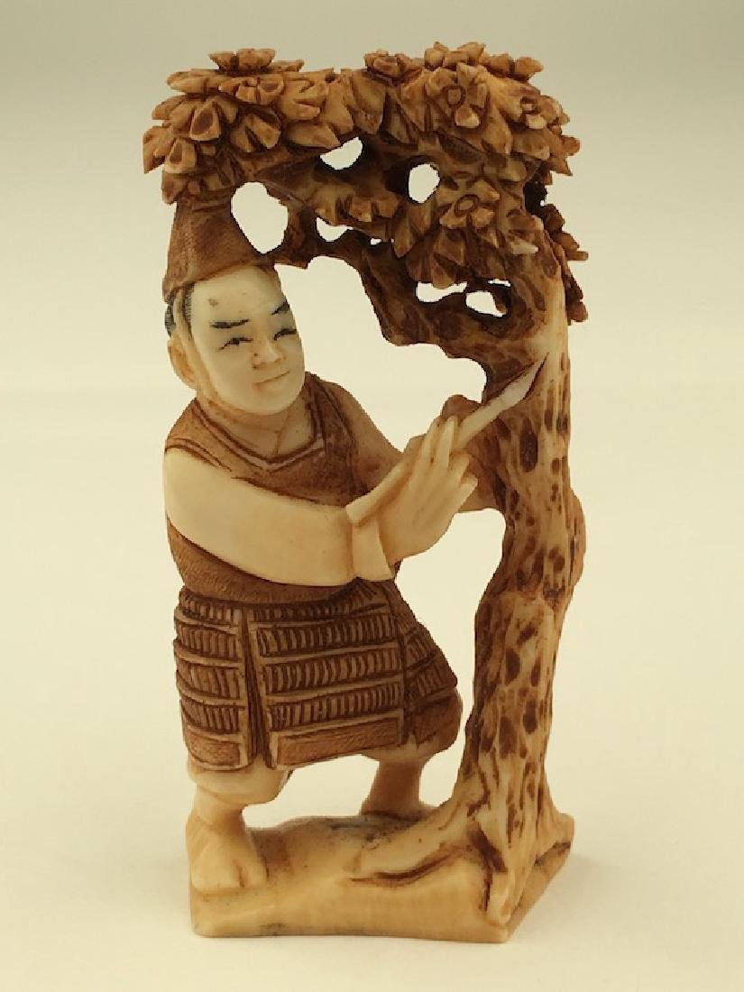 Antique carved Netsuke figure of a man under a lotus