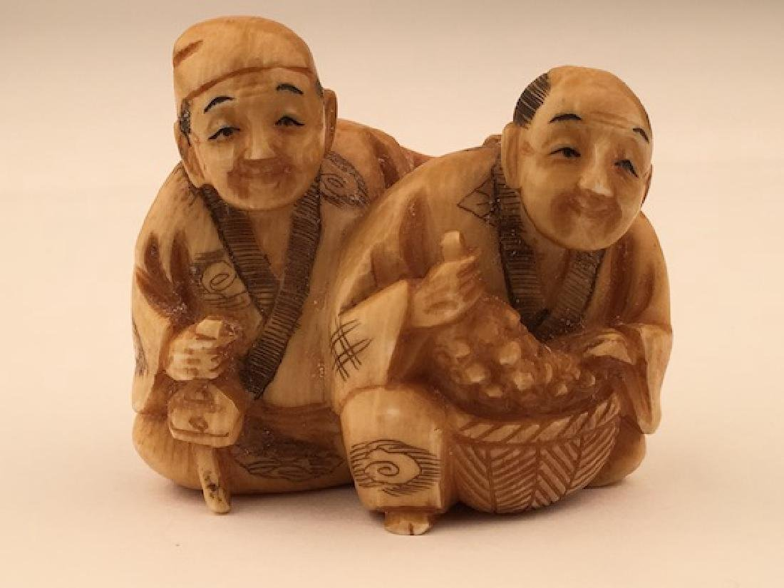Antique carved Netsuke figure of a man and lady with a