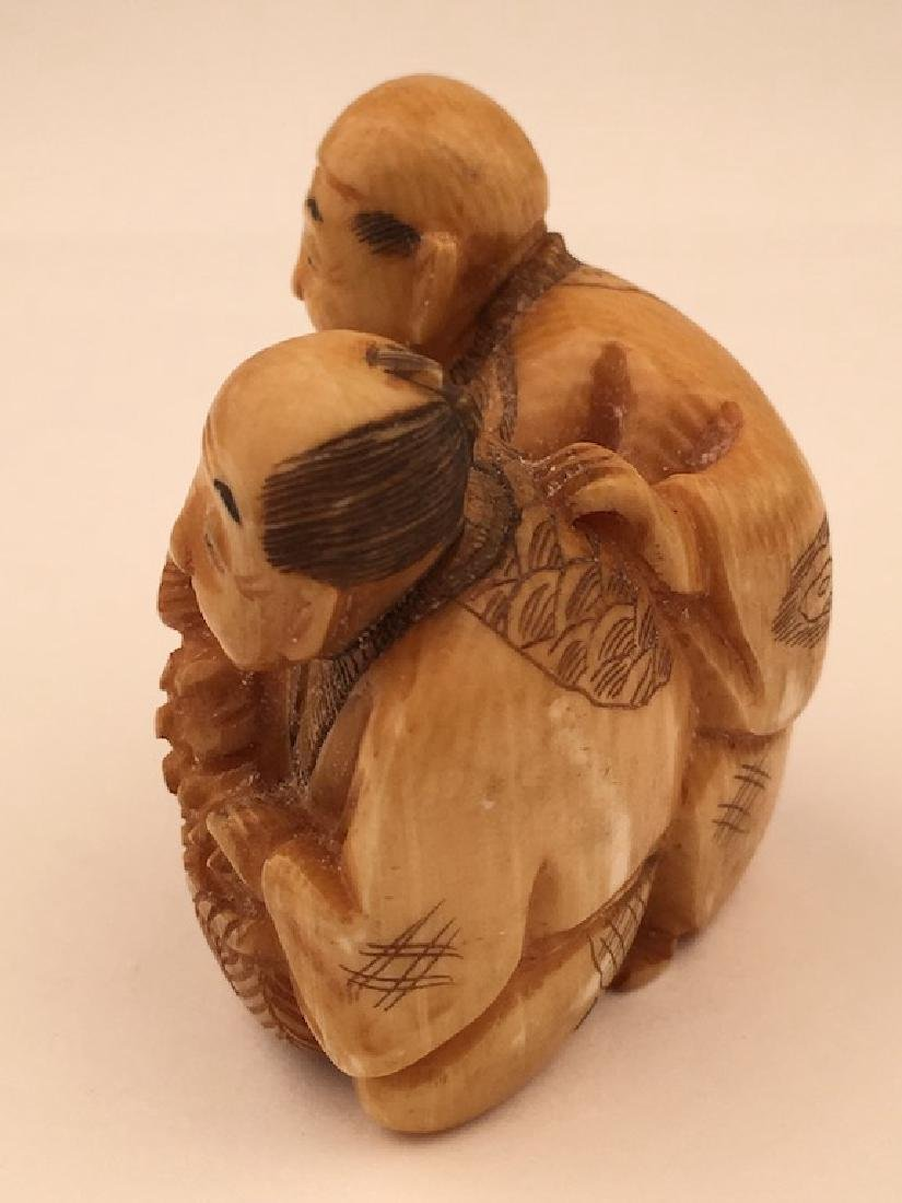 Antique carved Netsuke figure of a man and lady with a - 2