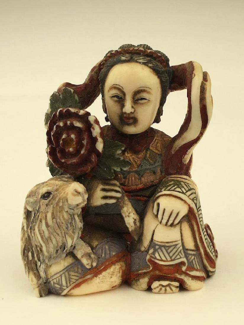 Antique carved Netsuke figure of a lady sitting next to