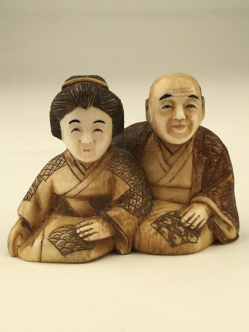 Antique carved Netsuke figure of a man and lady sitting