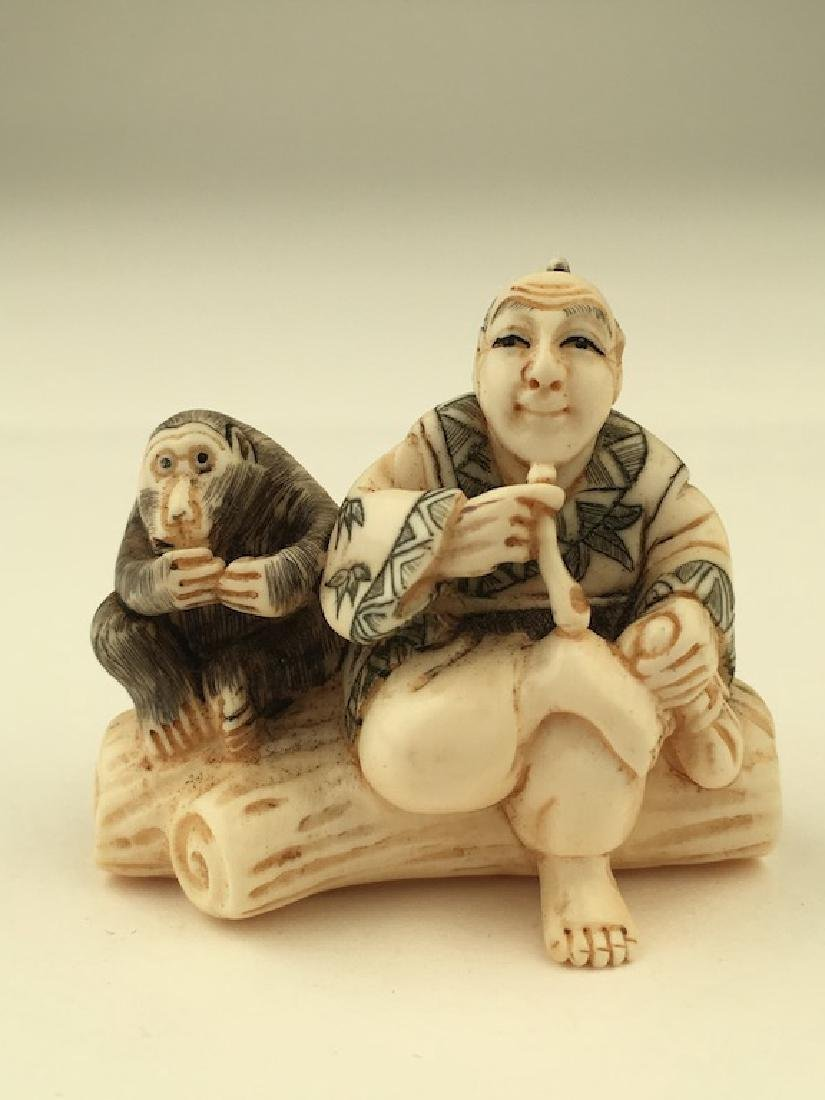 Antique carved Netsuke figure of a man and monkey
