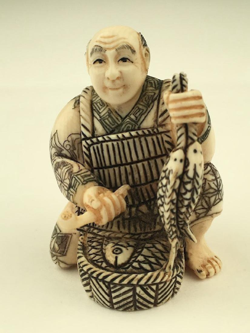 Antique carved Netsuke figure of a man with a basket of
