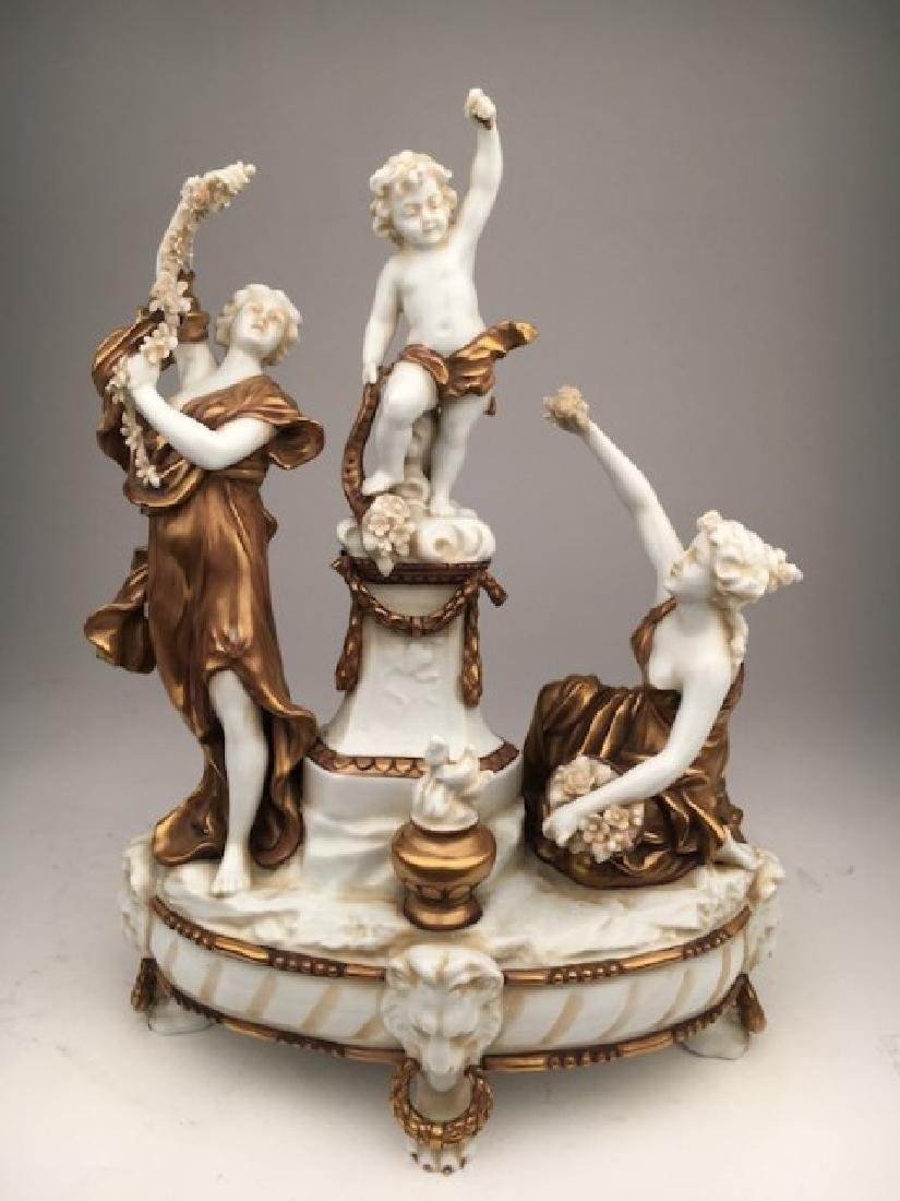 Porcelain figurine of two women and one putti all with