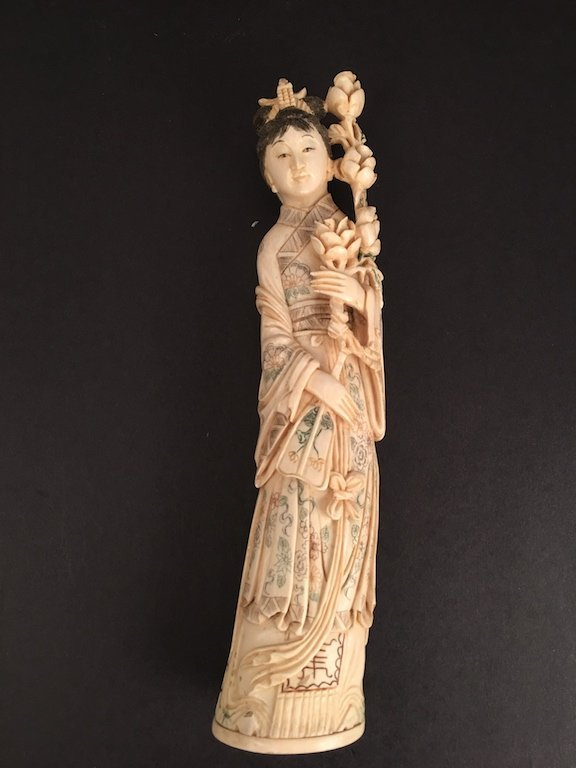 Antique carved standing beauty holding a bunch of